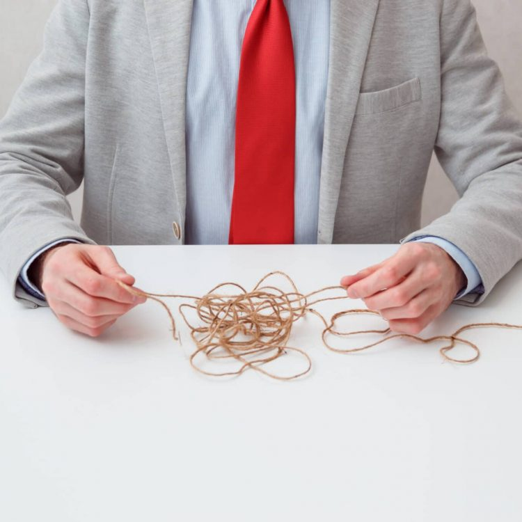 A lone businessman try to unwinds tangled thread ball like puzzle out situation. Conceptual photo. No face.