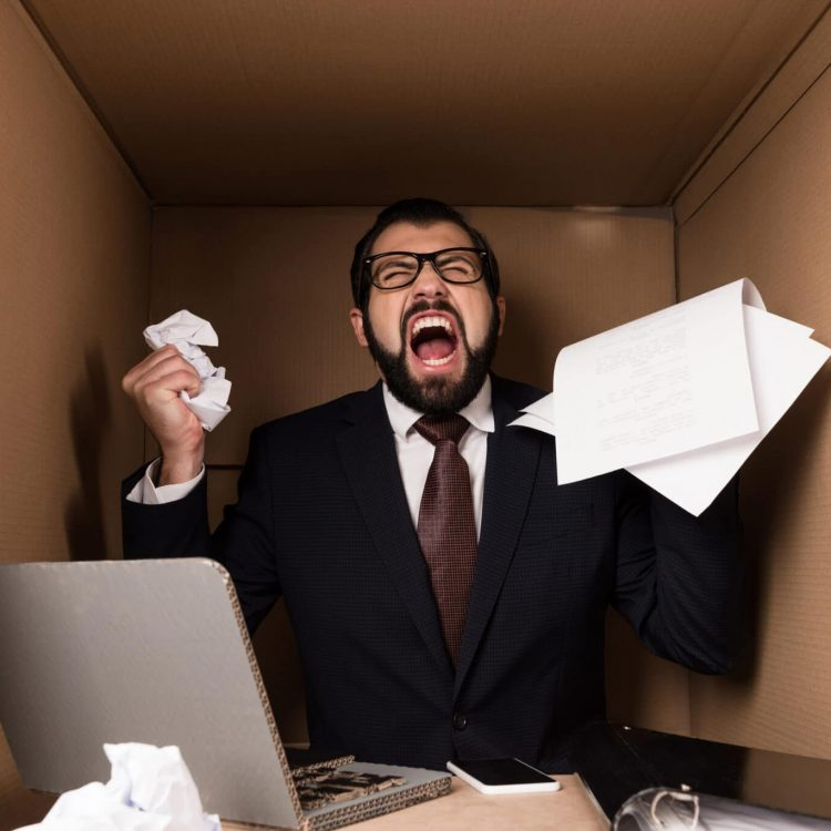 angry businessman yelling and working with documents and cardboard laptop in box