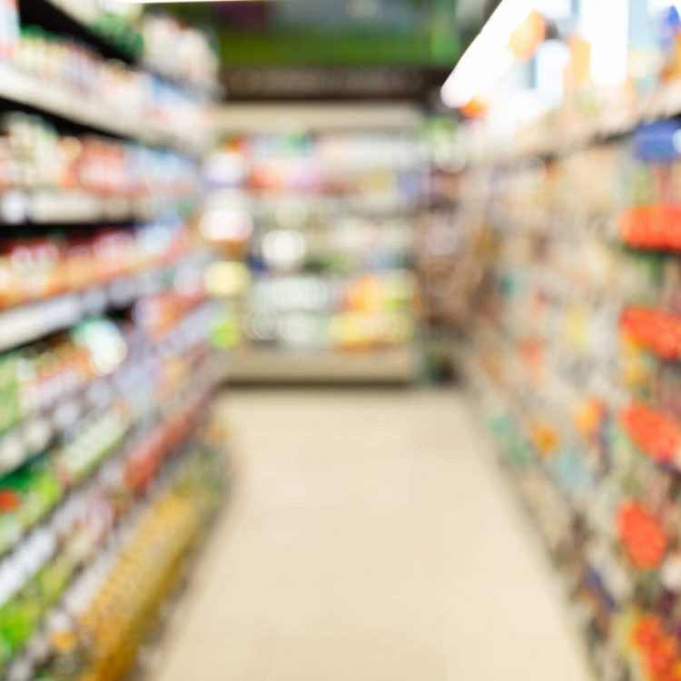 Blurred Supermarket Background, Grocery Store Aisle With Colorful Shelves And Food Products. Shopping Concept. Abstract Defocused Shot Of Groceries Shop Warehouse With No People