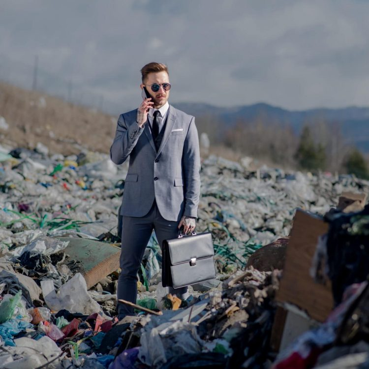 Fashionable modern businessman with smartphone on landfill, consumerism versus pollution concept.