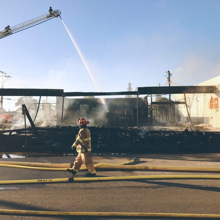 fireman-walking-past-burned-out-building-NK6UNBA