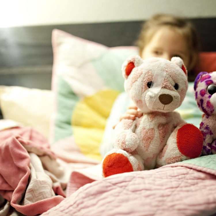 girl-playing-with-stuffed-animals-in-bed-TF6MNYL