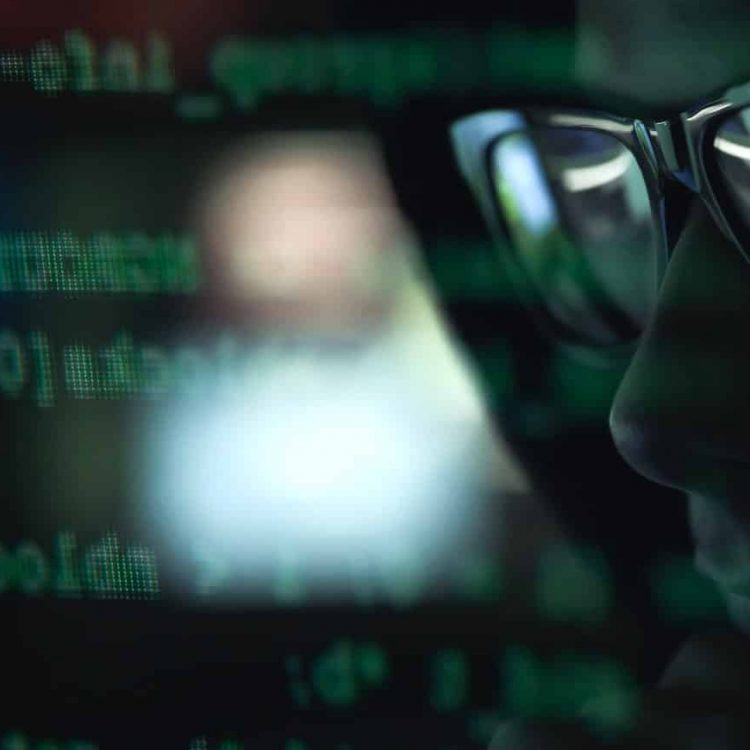 hacker-with-sunglasses-and-code-on-the-screen-34EWK89-2