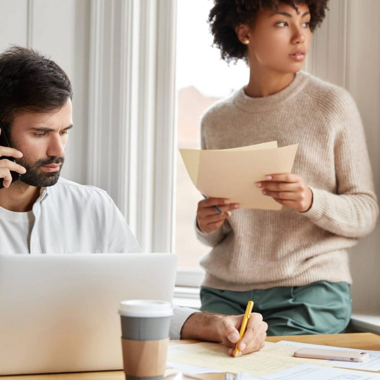 Hard working freelancer uses modern technologies, solves problems on distance, writes some information in papers, sits at work place, African woman stands in background, helps with financial report