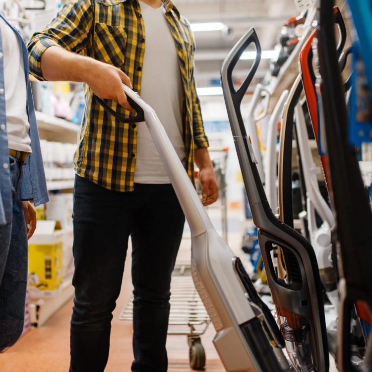 Male person hand holds vacuum cleaner in electronics store. Man buying home electrical appliances in market