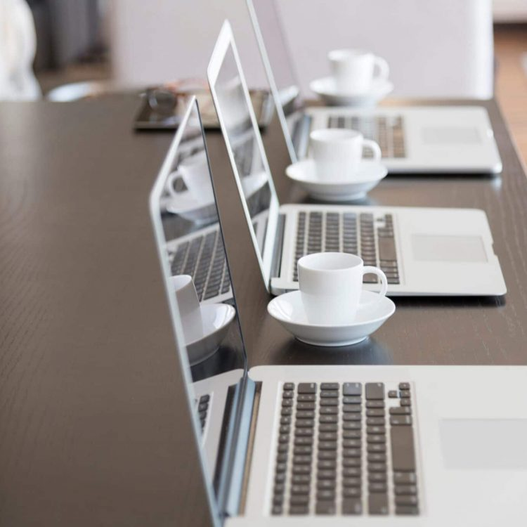 multiple-computers-on-conference-table-with-lines--CHRMFQ7