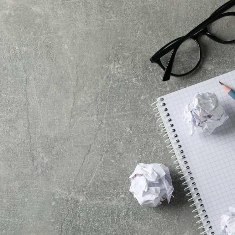 Paper balls, notebook, glasses and pencils on grey table, top view