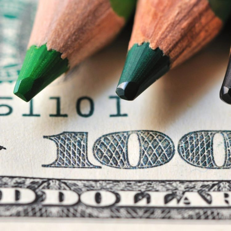 Photo of wooden pencils in bright green and purple colors against the background of a dollar bill