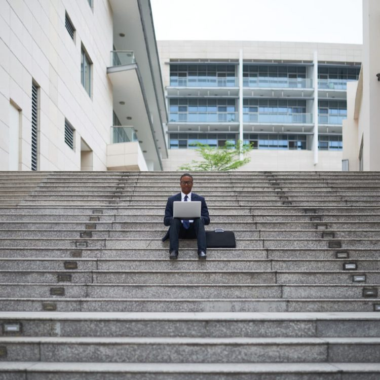 Young project manager of IT company sitting steps outdoors and working on documents and contract before meeting with colleagues