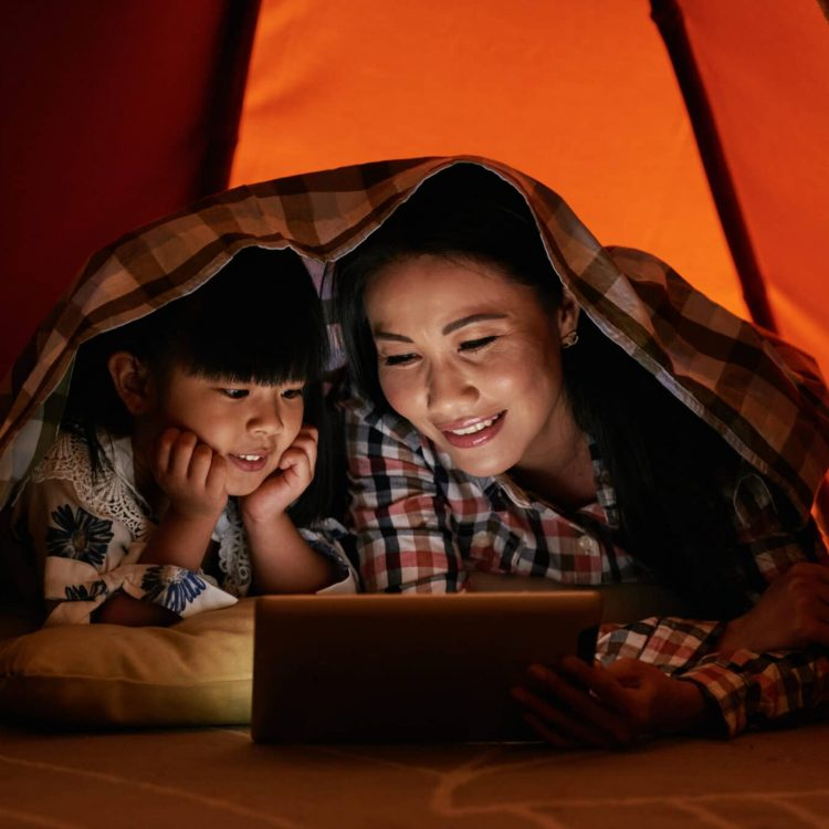 Smiling Asian woman reading e-book to her little daughter