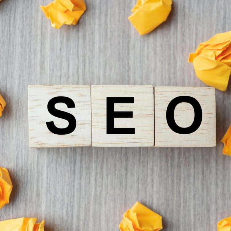 SEO (Search Engine Optimization) text wood cubes with crumbled paper on wooden table background. Idea, Vision, Strategy, Analysis, Keyword and Content concept