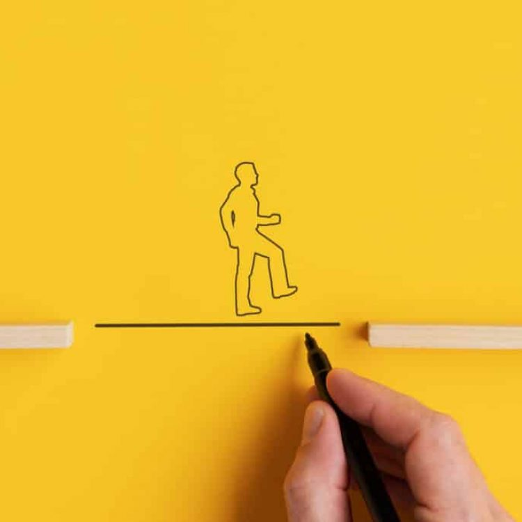 Wide view image of male hand drawing a line between two wooden pegs for a silhouette of a man to walk across. Over yellow background with copy space.