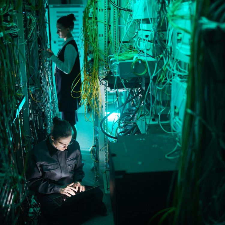Portrait of young technician setting up computer network in server room, copy space