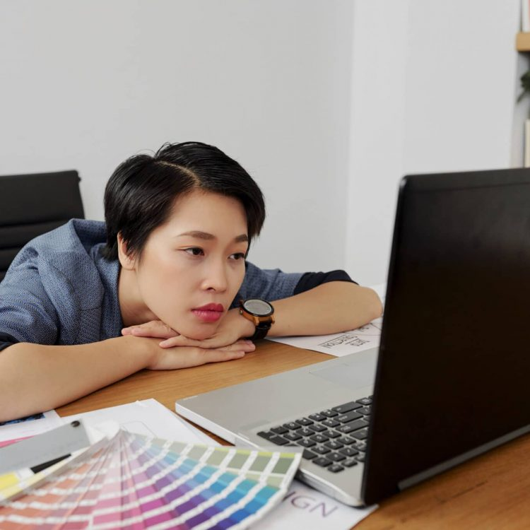 Tired web designer reading e-mail with corrections from client on laptop screen