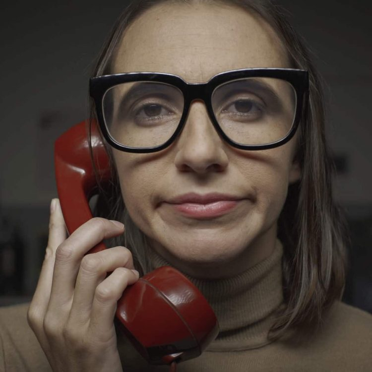 Disappointed woman with glasses having a boring phone call